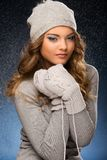 Cute curly girl wearing mittens during snowfall Stock Image