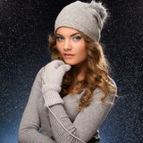 Cute curly girl wearing mittens during snowfall Stock Photos