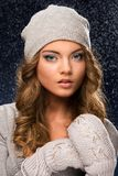 Cute curly girl wearing mittens during snowfall Royalty Free Stock Photography