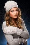 Cute curly girl wearing mittens during snowfall Royalty Free Stock Images