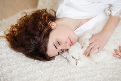 Cute curly hair woman in a white silk dressing gown in the early morning playing with white fluffy cat sitting on sofa Royalty Free Stock Image