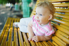 Cute curly haired baby girl on bench Stock Images