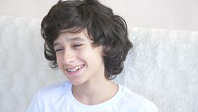 Cute curly-haired boy the teenager looks into the camera laughing and makes a funny facial expression. 4k, slow motion stock video footage