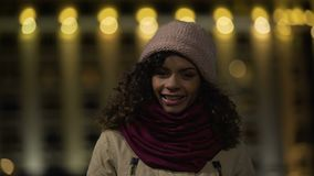 Cute curly-haired casual girl posing and sincerely smiling at camera, happy lady stock footage