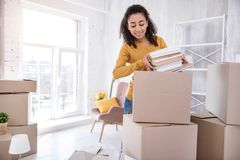 Cute curly-haired girl packing books before moving out