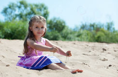 Cute curly-haired girl plays with sand Royalty Free Stock Photo