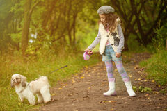 Cute curly-haired girl walking with dog in park Royalty Free Stock Image