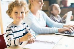 Cute Curly Haired Kid Writing stock photography