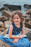 Cute curly happy child girl relaxing on stone beach, wrapped in cozy quilt blanket. Stock Photos