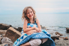 Cute curly happy child girl relaxing on stone beach, wrapped in cozy quilt blanket. Royalty Free Stock Photos