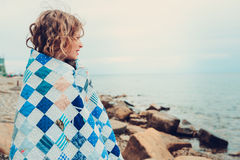 Cute curly happy child girl relaxing on stone beach, wrapped in cozy quilt blanket. stock image