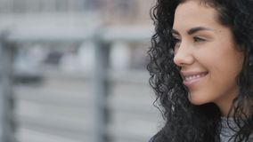 Cute curly lady at the street. Close-up. The camera focuses on the young brunette curly woman at the street. Attractive lady smiles and looks around herself stock footage