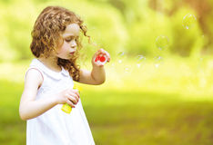 Cute curly little girl blowing soap bubbles outdoors