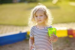 Cute curly little girl playing in the sandbox alone and away from everyone royalty free stock photo