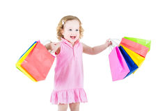 Cute curly little girl after sale with her colorful bags Stock Images