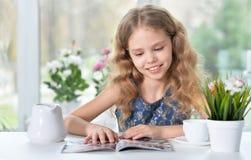 Little girl reading magazine. Cute curly little girl sitting at table and reading magazine Stock Photos