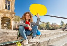 Cute teen sitting on the steps with speech bubble. Cute curly teenage boy sitting on the steps outdoors, holding yellow blanked speech bubble over head Stock Photo