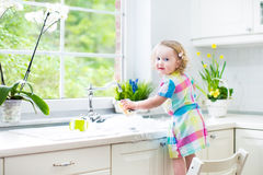 Cute curly toddler girl in colorful dress washing dishes Stock Photos