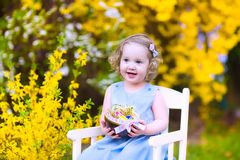 Cute curly toddler girl enjoying egg hunt in the garden Royalty Free Stock Image