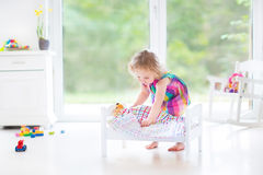 Cute curly toddler girl playing with her bear Royalty Free Stock Image