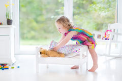 Cute curly toddler girl playing with her teddy bear Royalty Free Stock Photos