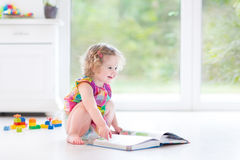 Cute curly toddler girl reading book in sunny bedroom Stock Image