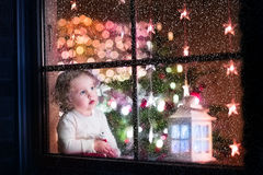 Cute curly toddler girl sitting with a toy bear at home during Christmas time, preparing to celebrate Xmas Eve. View through a window from outside into a Royalty Free Stock Images
