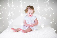 Cute curly toddler girl in a white dress on bed between Christmas lights Royalty Free Stock Photos