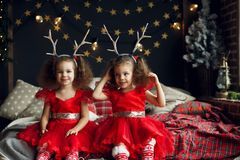 Cute curly twins girl sitting on the bed in decorated xmas room, on Christmas evening 2018 near New Year fir tree with royalty free stock photo