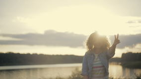 Cute curly young woman in a jeans jacket runs down the lakeside to the bright sunset, then turns to camera and smiles stock video footage