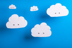 Cute cutout clouds hanging with sky blue background Stock Image