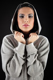 Cute in da hood. Beautiful brunette girl wearing hooded sweater and posing. She's holding the hood Stock Images