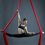 Cute dancer doing gymnastic split on aerial silks. Attractive dancer doing gymnastic split on aerial silks Stock Images