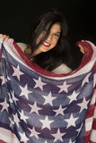 Cute dark complected woman holding an American flag scarf smilin. Cute dark woman holding American flag scarf Stock Photos