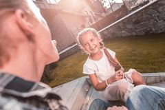 Cute dark-eyed beaming girl feeling extremely cheerful and funny royalty free stock photos