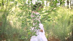 Cute dark-haired girl in a long white luxurious light vintage summer dress with a mesh and floral patterns walks along. The path in an amazing forest alone and stock video