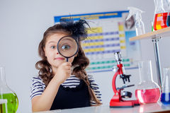 Cute dark-haired girl looking through magnifier Royalty Free Stock Photos