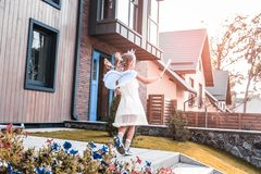 Cute dark-haired girl wearing fairy costume walking outside house royalty free stock image