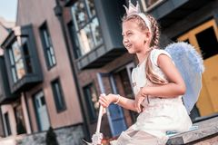 Cute dark-haired girl wearing fairy wings and little crown walking outside stock photo
