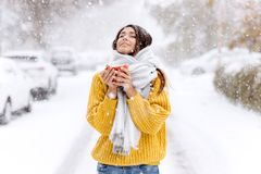 Cute dark-haired girl in a yellow sweater, jeans and a white scarf standing with a red mug on a snowy street on a winter. Day royalty free stock images