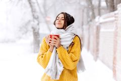 Cute dark-haired girl in a yellow sweater, jeans and a white scarf standing with a red mug on a snowy street on a winter. Day stock images