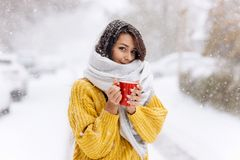 Cute dark-haired girl in a yellow sweater, jeans and a white scarf standing with a red mug on a snowy street on a winter. Day royalty free stock image
