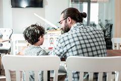Cute dark-haired son listening to his father while reading book together royalty free stock photography