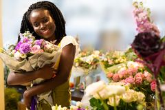 Cute dark-skinned girl holding big luxury flowers. It is mine. Joyful young woman expressing positivity while posing on camera stock image