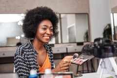 Cute dark-skinned woman with coral lipstick conducting online tutorial royalty free stock image