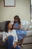 Cute daughter combing mothers hair in living room royalty free stock image