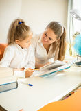 Cute daughter doing homework with mother Stock Photography