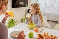 Cute daughter eating cereals with her mom royalty free stock image