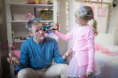 Cute daughter in fairy costume putting makeup on her fathers face royalty free stock image