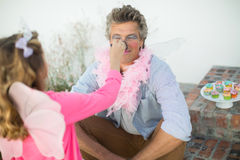 Cute daughter in fairy costume putting makeup on her fathers face royalty free stock photos